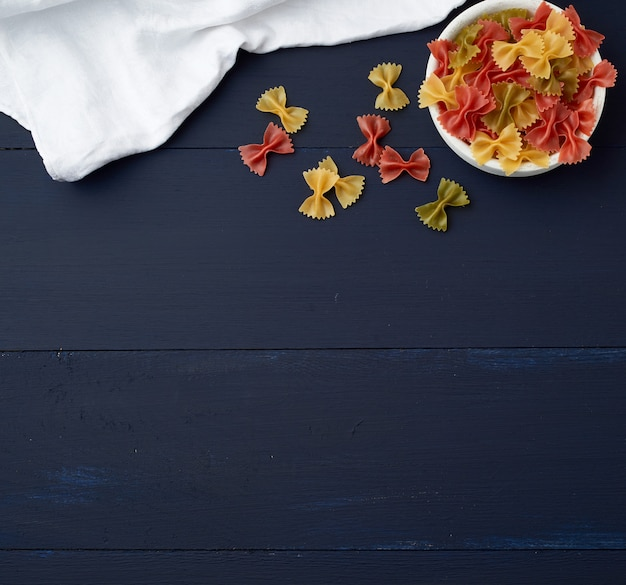 Raw pasta in the form of bows in a wooden round plate and white textile napkin on a blue wooden , top view. vegetarian nutrition. italian cuisine