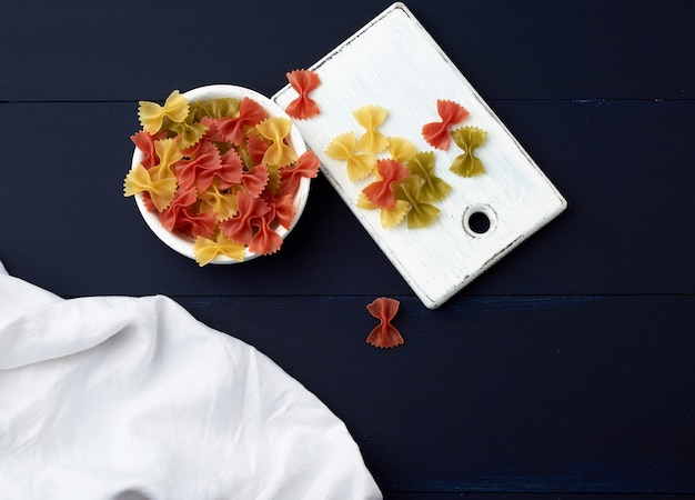 Raw pasta in the form of bows in a wooden round plate and white textile napkin