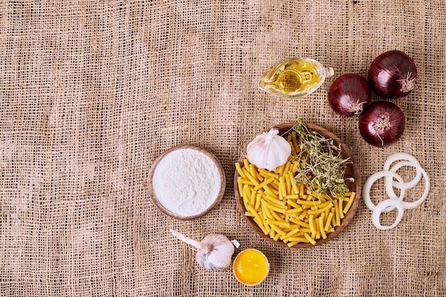 Pasta cruda, aglio e cipolle su panno marrone.