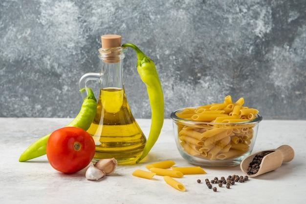 Pasta cruda in una ciotola di vetro, una bottiglia di olio d'oliva, grani di pepe e verdure sul tavolo bianco.