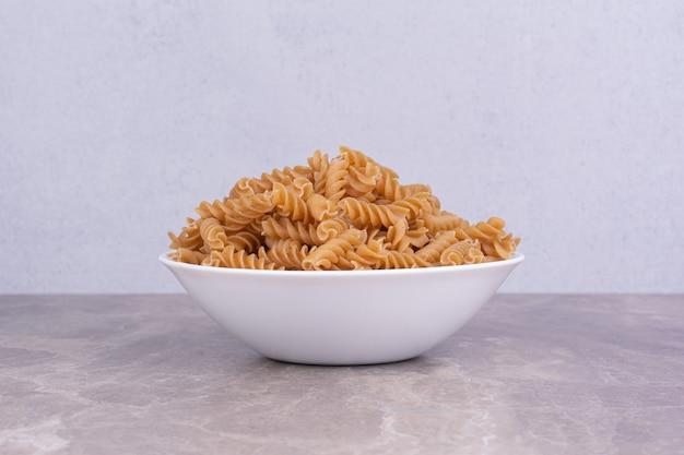 Сырая паста в белой керамической тарелке на мраморе