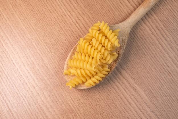 Сырые макароны в деревянной ложкой на деревянный стол