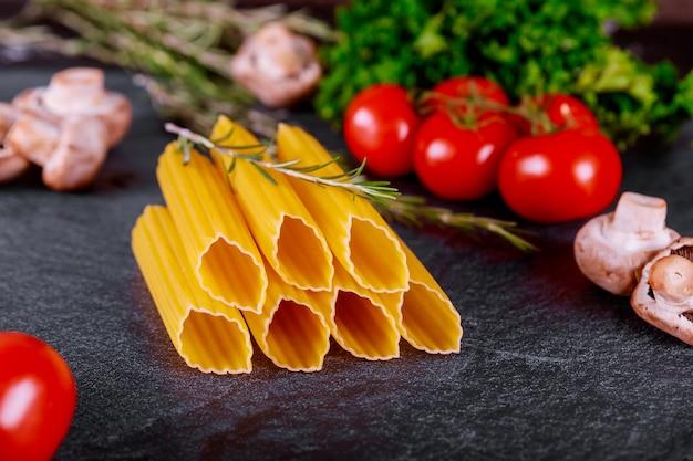 Сырые макароны маникотти с помидорами, грибами и розмарином