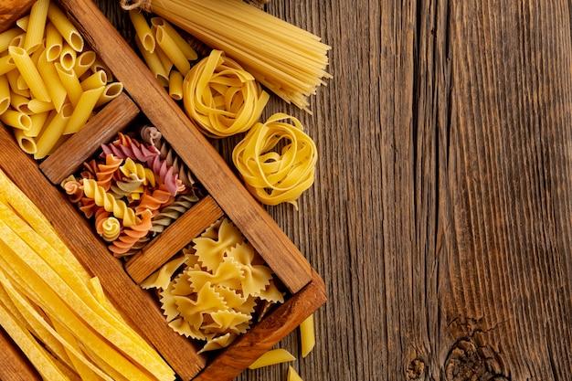 Сырье макароны на деревянных фоне с копией пространства
