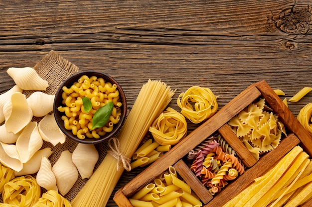 Raw pasta mix on wooden background