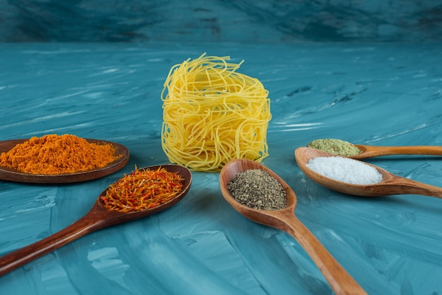 Raw pasta nest with spoons of condiments on blue surface