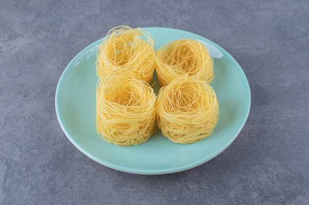 Raw pasta nests on blue plate.