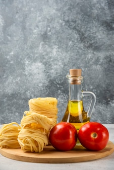 Гнезда сырых макарон, бутылка оливкового масла и помидоры на деревянной тарелке.