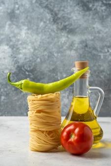 Сырые гнезда макаронных изделий, бутылка оливкового масла и овощей на белом столе.