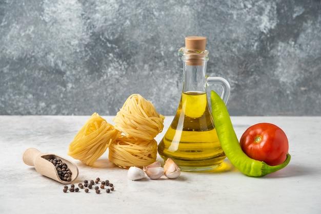 白いテーブルに生パスタの巣、オリーブオイルのボトル、コショウの穀物と野菜。