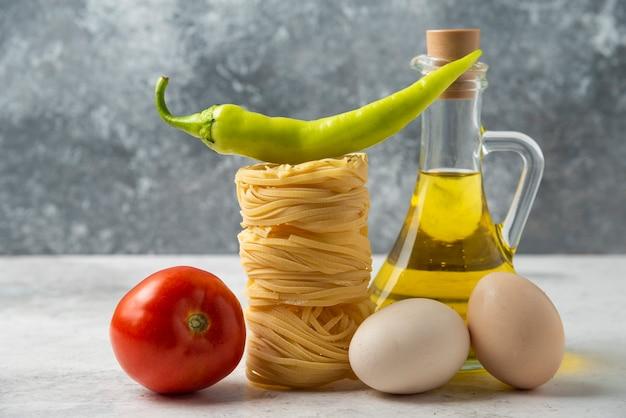 Nidi di pasta cruda, bottiglia di olio d'oliva, uova e verdure sulla tavola bianca.