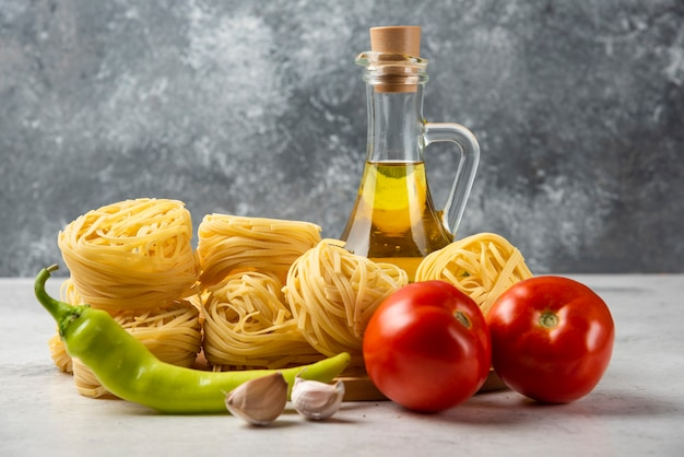 Raw pasta nests, bottle of olive oil and vegetables on white table.
