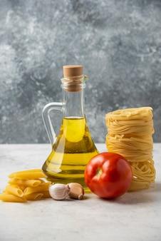 Nidi di pasta cruda, bottiglia di olio d'oliva e verdure sulla tavola bianca.