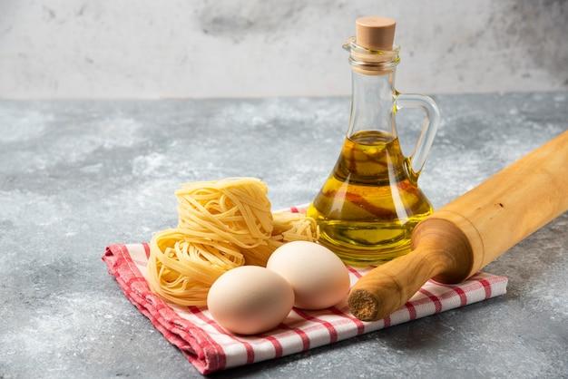 Гнезда сырых макарон, яйца, бутылка оливкового масла и скалка на мраморном столе.