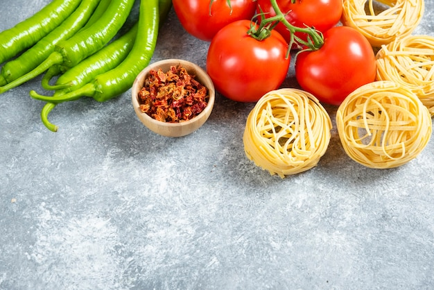 Raw pasta nests and ripe vegetables on marble background.