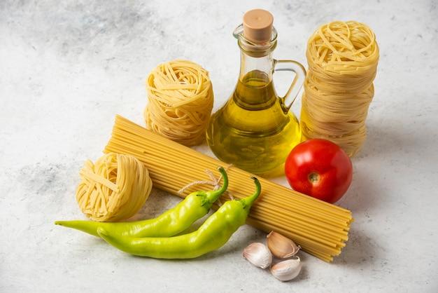 白い表面に生パスタの巣、スパゲッティ、オリーブオイルと野菜のボトル。