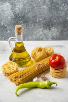 Nidi di pasta cruda, spaghetti, bottiglia di olio d'oliva e verdure su superficie bianca.