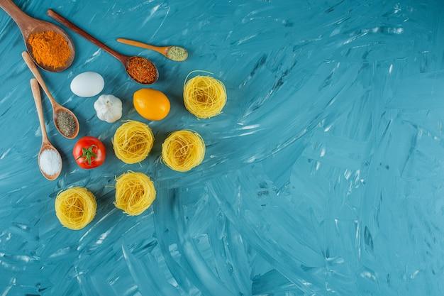 Nidi di pasta cruda con condimenti e verdure su superficie blu.