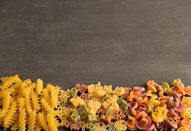 사진 아래의 어두운 나무 테이블에 다양한 색상과 유형의 생 파스타가 놓여 있습니다.