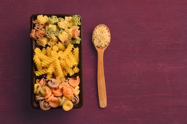 다양한 색상의 생 파스타가 상자에 놓여 있고 그 옆에는 버미첼리가 든 숟가락이 놓여 있습니다