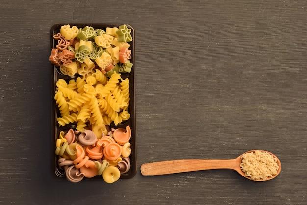 さまざまな色、種類、サイズの生パスタが箱の中に配置され、その隣に春雨のスプーンがあります