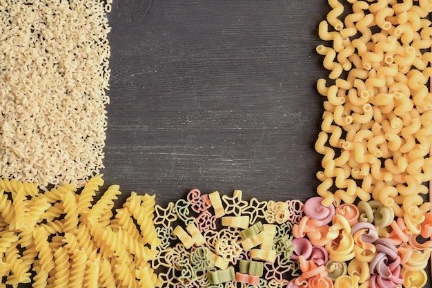 다양한 색상, 유형 및 크기의 생 파스타가 어두운 나무 탁자에 놓여 있습니다.