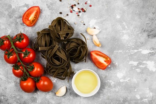 Сырые макароны тальятелле со шпинатом и ингредиенты для приготовления пищи (помидоры черри, специи, чеснок) на сером фоне. вид сверху, скопируйте пространство. пищевой фон