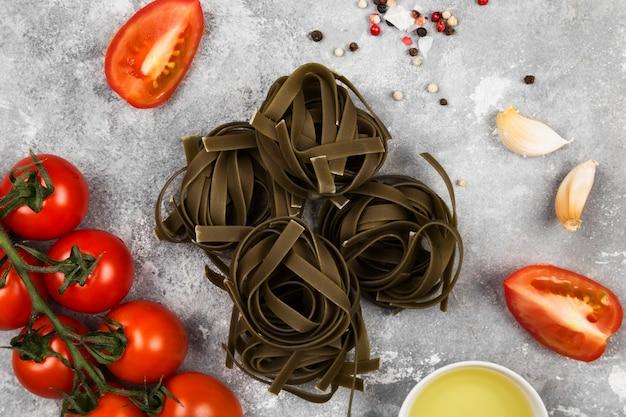 Сырые макароны тальятелле со шпинатом и ингредиенты для приготовления пищи (помидоры черри, специи, чеснок) на сером фоне. вид сверху. пищевой фон