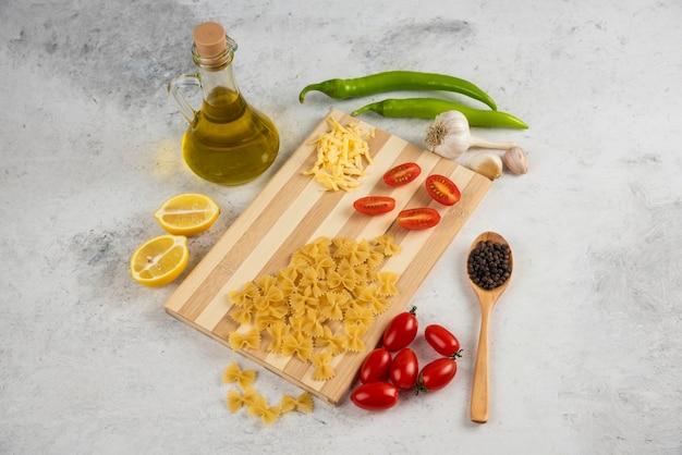Сырая паста, масло и свежие овощи на мраморе.
