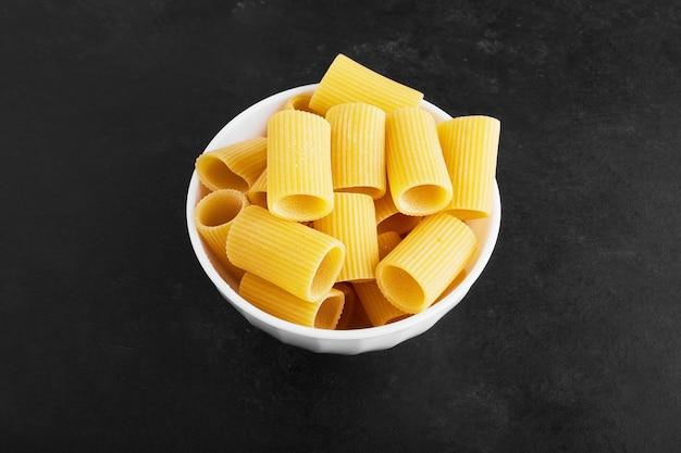 Сырые макароны на черном в белой чашке.