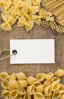 Raw pasta and price tag label on wooden