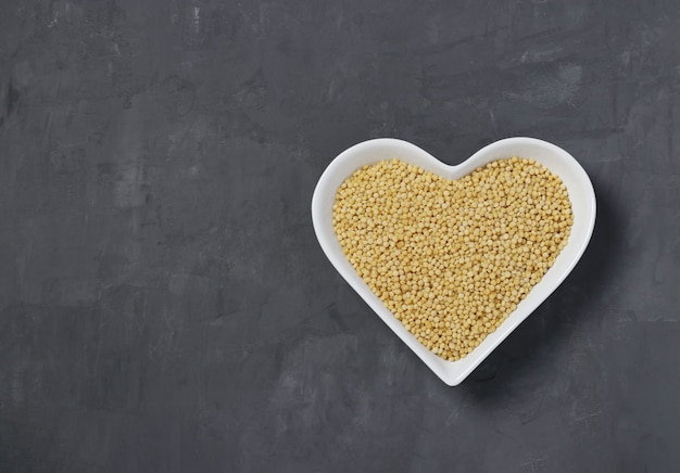 Raw pasta ptitim on heart-shaped plate on dark gray table
