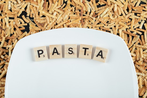 Raw pasta scattered around white plate with wooden letters. high quality photo