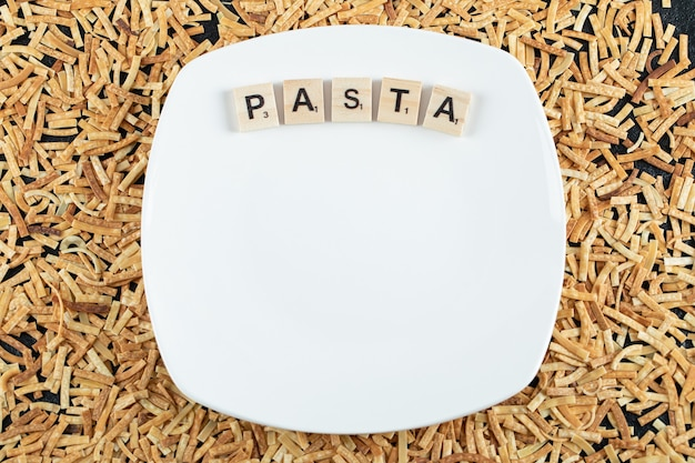 Raw pasta scattered around white plate with wooden letters.