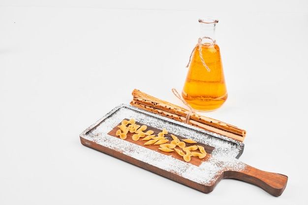 Сырые макароны, разбросанные по деревянной доске с бутылкой масла и крекерами на белом
