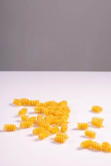 Raw pasta scattered on a white background, minimalistic.