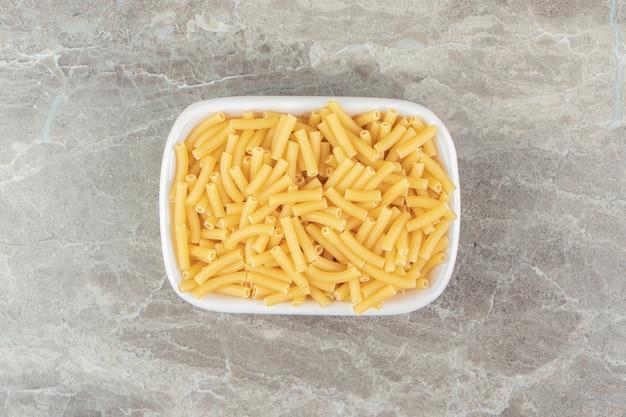 Raw pasta shaped like narrow tubes in white bowl