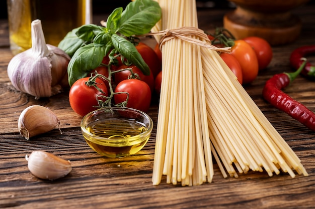 Raw pasta spaghetti with tomatoes, garlic olive oil basil on old rustic wooden background