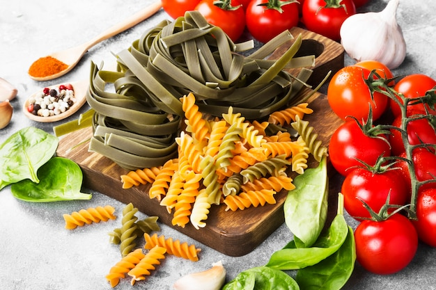 Raw pasta of tagliatelle with spinach and fusilli pasta with spinach and tomatoes