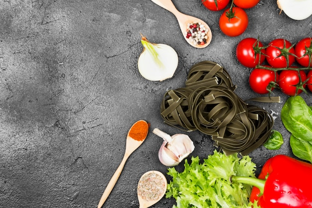 Raw pasta of tagliatelle with spinach and ingredients for cooking