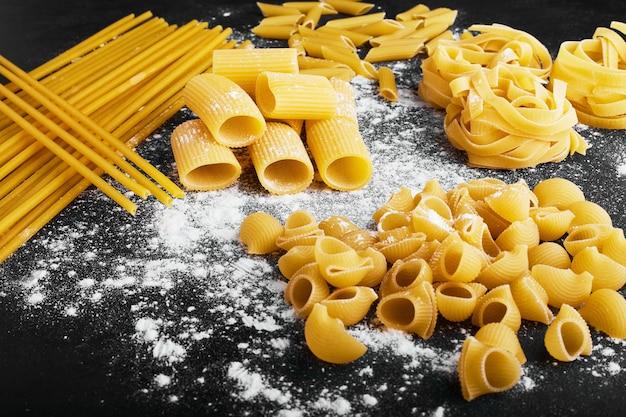 Varietà di pasta cruda su una superficie ricoperta di farina.
