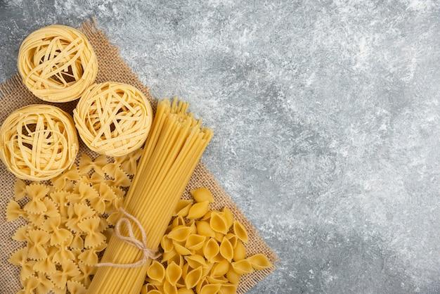 Varietà di pasta cruda su un pezzo di tela.