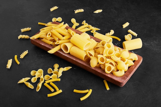 Raw pasta varieties on a wooden platter.