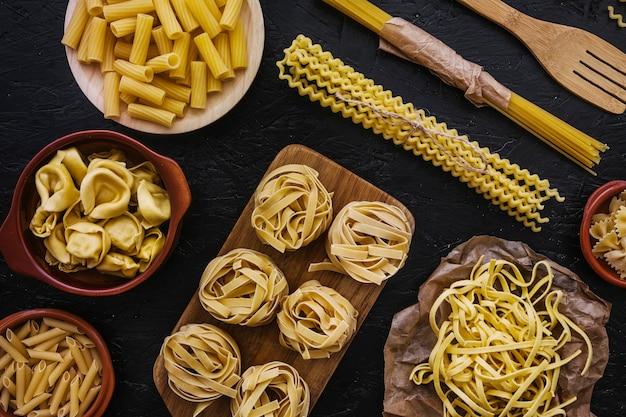 Raw pasta in various kitchenware