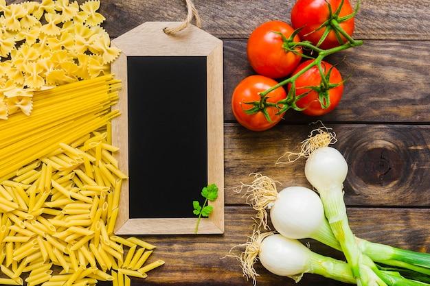 Raw pasta and vegetables near blackboard Free Photo