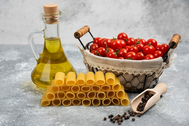 Сырая паста с корзиной помидоров черри и бутылкой оливкового масла.
