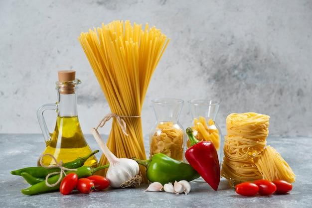 Сырые макароны со стеклянной бутылкой масла и овощей.