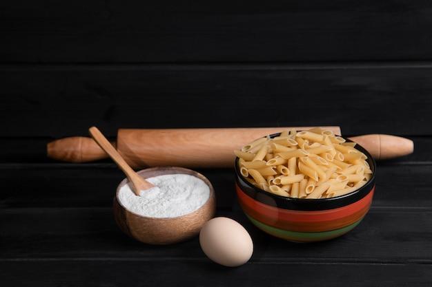 木製のテーブルに小麦粉と鶏卵を置いた生パスタ。高品質の写真