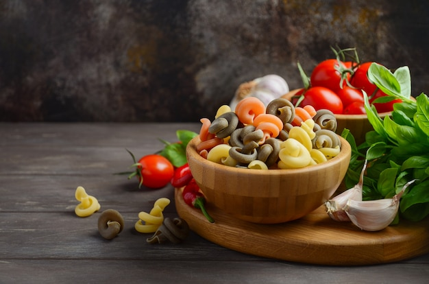Raw pasta with fresh cherry tomatoes, basil, chili pepper and garlic for italian food.