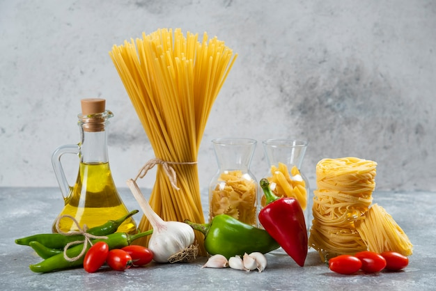 Raw pasta with a glass bottle of oil and vegetables.